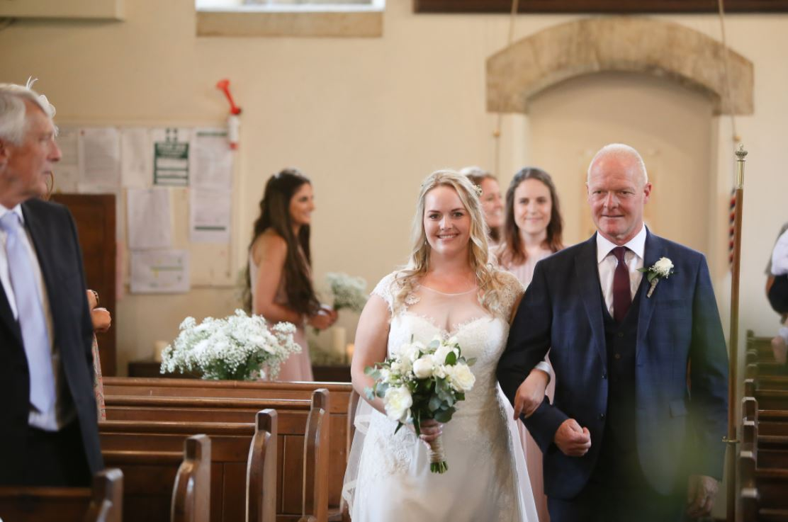 Chloe making her way to her wedding ceremony on the arm of her father.